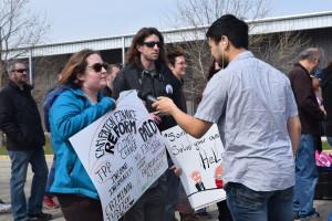 WSUM News Team member Kai Brito interviews people waiting in line to see Sanders. Photo Credit Kelly Wang WSUM